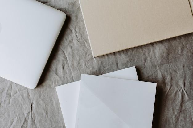 Минимальная рабочая поверхность с ноутбуком, лист бумаги на серой вымытой льняной скатерти