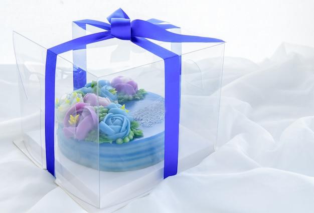 パンダンレイヤースウィートケーキから作られた最小限のケーキと白い布のプラスチックの箱に飾られたワイトかわいい花。