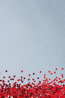 Minimal christmas background with red confetti on grey