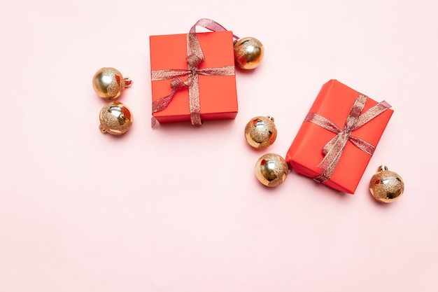Minimal christmas newyear  of christmas red gift boxes, balls on pastel pink .