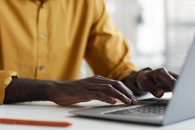 オフィスの白い机に座って、男性の手のタイピング、コピースペースに焦点を当てながらラップトップを使用して現代のアフリカ系アメリカ人男性の最小限のクローズアップ