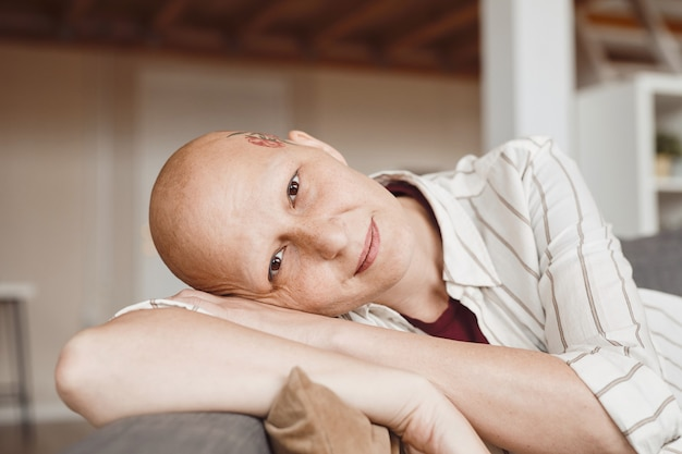 Minimal close up portrait of bald adult woman smiling at camera while lounging on couch in warm-toned home interior, alopecia and cancer awareness, copy space