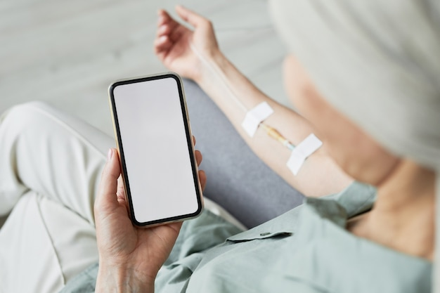 Minimal close up of unrecognizable woman getting iv drip and using smartphone with blank screen, copy space