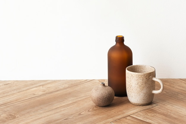 Minimal coffee cup by a brown vase on wooden floor