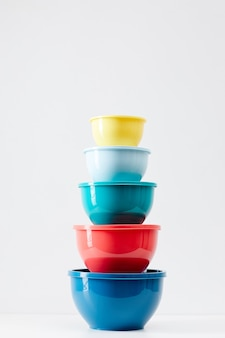 Minimal composition of colorful food containers stacked in row, plastic storage and recycling concept