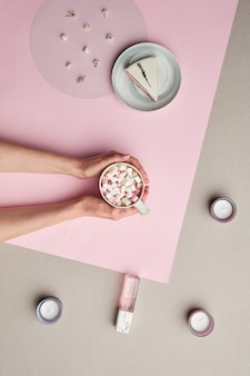 Minimal composition of female hands holding cup of sweet cocoa over pink graphic background,