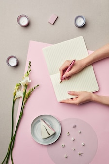 Minimal composition of female hands writing in blank planner over pink graphic background with floral decor,