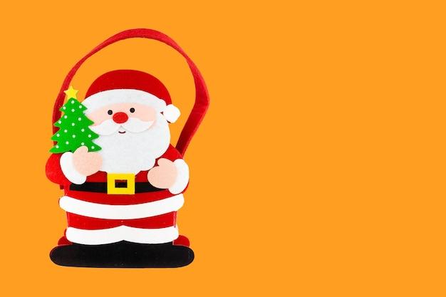 オレンジ色の背景にクリスマスサンタクロースで作られた最小限の構成。上面図。休日の新年のコンセプト。クリスマスプレゼント、おめでとうございます