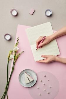 Минимальная композиция женских рук, пишущих в пустой планировщик на розовом графическом фоне с цветочным декором,