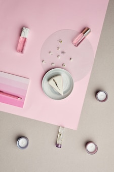 ピンクのグラフィックの背景に香水瓶とケーキの最小限の構成、