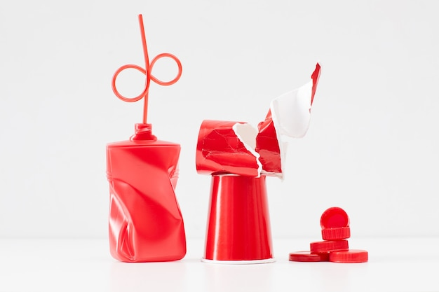 Minimal composition of red plastic items isolated, waste sorting and recycling concept