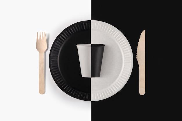 黒と白の紙皿、黒と白の表面にカップと木製のフォーク、上面図の最小限の構成。