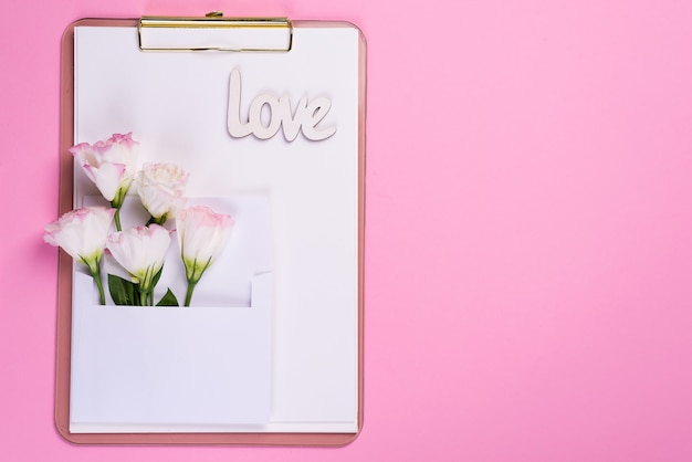Minimal composition with a eustoma flowers in an envelope on clipboard on a pink background, top view. valentines day, birthday, mother or wedding greeting card