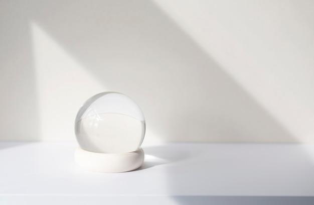 흰색 책상에 유리 공이 있는 최소한의 구성, 내부 장식으로 유리 글로브 공. 벽의 추상 그림자 선, 텍스트 공간, 모형