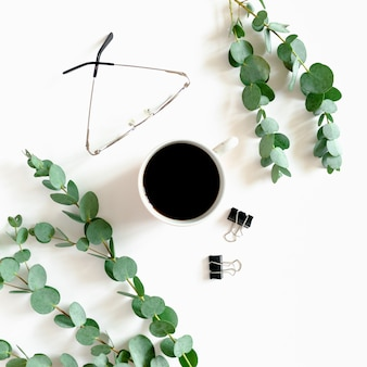 Minimal composition with mug of coffee, paper clips, glasses, eucalyptus branches on a white background