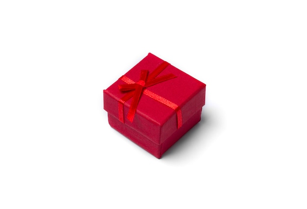 Minimal composition with red christmas gift box at white table
