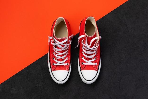 검은 색과 빨간색 배경에 여름 신발과 최소한의 구성. 복사 공간 평면 위치 평면도 빨간색 운동화. 패션 쇼핑 판매 개념