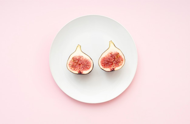 Minimal composition with two parts of figs on a white ceramic plate