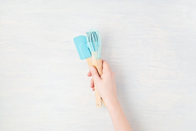 Minimal composition with womanhand holding kitchen utensils with copy space. healthy eating, home cooking, online recipes, internet classes concept. mockup, top view, flat lay