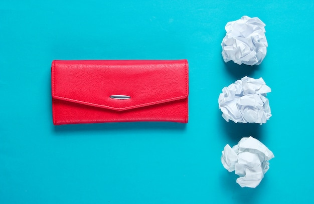 最小限のコンセプト。しわくちゃの紙のボール、青いテーブルに赤い革の財布
