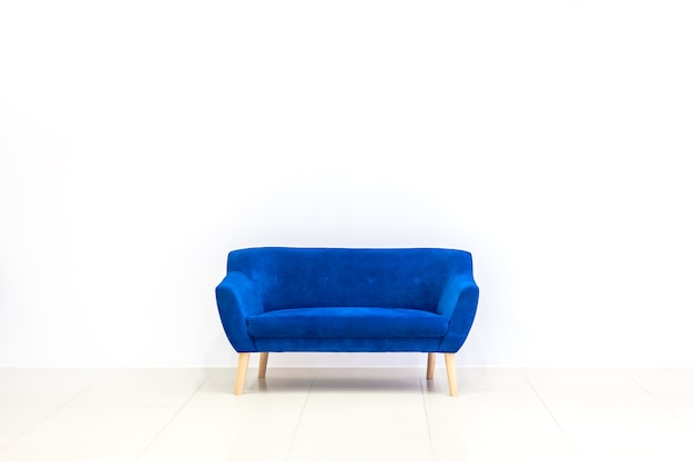 Minimal concept of living interior with bright blue sofa on white floor and background. scandinavian style wall mockup.