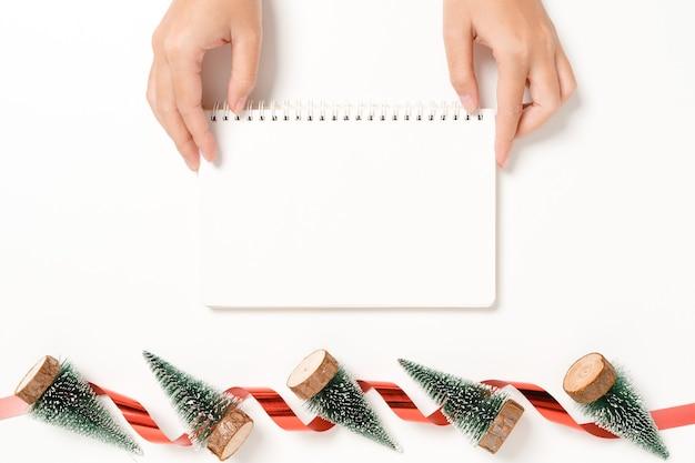 冬のクリスマスの伝統的な構成と新年の最小限の創造的なフラットレイ。上面図は、白い背景のコピースペースにテキスト用のモックアップ黒いノートブックを開きます。