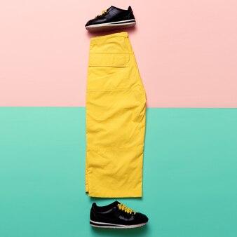 最小限のデザイン。パンツとスニーカー。明るい夏の服