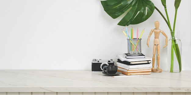 Minimal designer workplace with camera and office supplies on white table