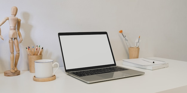 Minimal designer workplace with open blank screen laptop computer