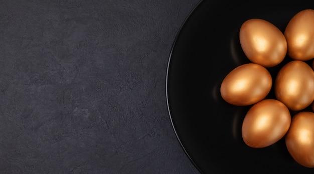 最小限のイースターバナー。黒い大理石の背景に分離された黒いプレートにスタイリッシュなイースターゴールデン装飾卵