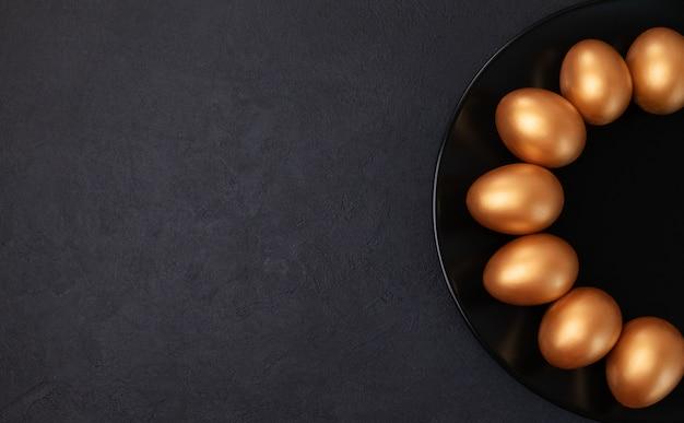 最小限のイースターコンセプト。黒い大理石の背景に分離された黒いプレートにスタイリッシュなイースターゴールデン装飾卵