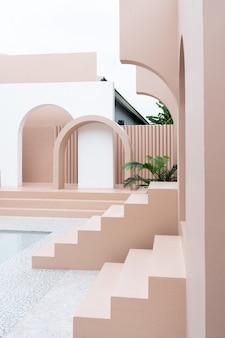 Минимальная пустая космическая сцена с розовой краской стен, аркой, розовой лестницей и искусственным кактусом