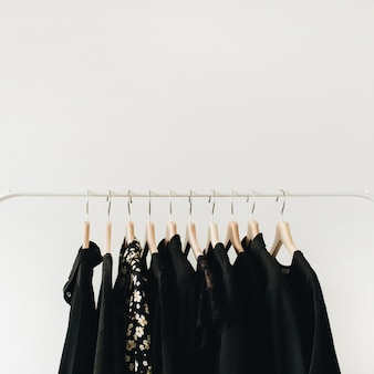 Minimal fashion clothes concept. black female blouses and t-shirts on hanger on white.