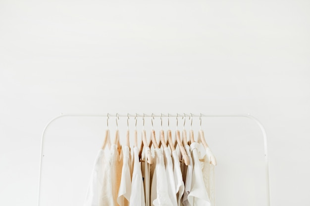 Minimal fashion clothes concept. female blouses and t-shirts on hanger on white