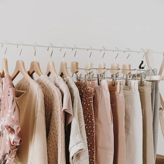 最小限のファッション服のコンセプト。白のハンガーにスタイリッシュな女性のブラウス、セーター、パンツ、ジーンズ、tシャツ