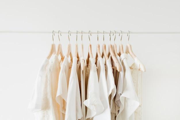 最小限のファッション服のコンセプト。白のハンガーに白い女性のブラウスとtシャツ。