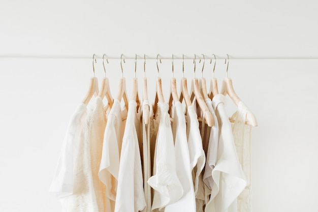 Minimal fashion clothes concept. white female blouses and t-shirts on hanger on white.