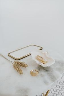 Минимальная модная композиция с золотыми серьгами в ракушке на мраморном столе с зеркалом и стеблями пшеницы. концепция бижутерии.