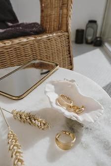 Минимальная модная композиция с золотыми серьгами в ракушке на мраморном столе со стеблями пшеницы.