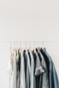 最小限のファッションコンセプト。白のハンガーの女性の服