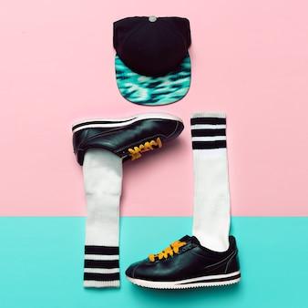 最小限のファッションクリエイティブアート。スタイリッシュなスニーカーと靴下。キャップ。通りの振動