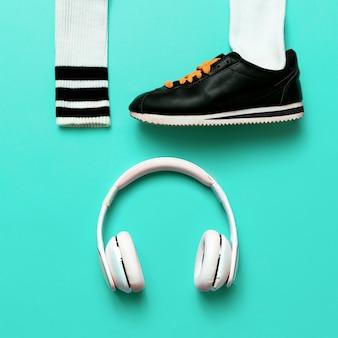 最小限のファッションクリエイティブアート。アーバンストリートの振動。音楽とスポーツ。スニーカーとヘッドホン。