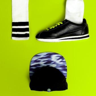 最小限のファッションクリエイティブアート。アーバンストリートの振動。スポーツ。スニーカーとキャップ