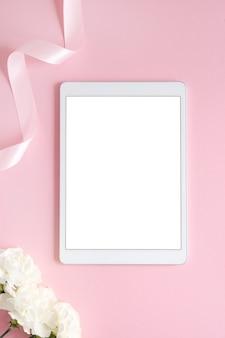 분홍색과 흰색 꽃과 빈 화면이 있는 태블릿이 있는 최소한의 여성용 플랫. 창백한 복숭아 배경에 스타일이 지정된 모의 위쪽 보기. 기기 수직
