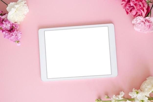 분홍색과 흰색 꽃과 빈 화면이 있는 태블릿이 있는 최소한의 여성용 플랫. 창백한 복숭아 배경에 스타일이 지정된 모의 위쪽 보기. 장치