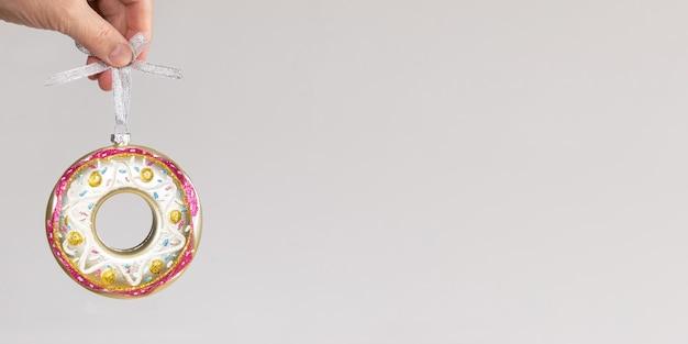 ニュートラルグレーにカラフルなクリスマスのおもちゃのガラスドーナツを持っている女性の手で最小限のお祝いのクリスマスバナー。スペースをコピーします。