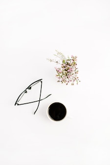 Minimal flat lay, top view composition with glasses, coffee cup and wildflowers on white background