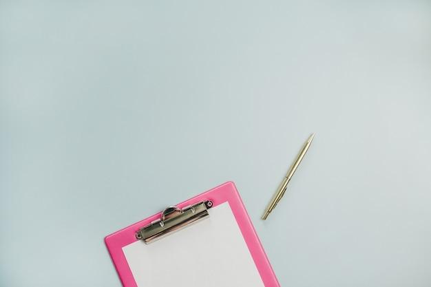 最小限のフラットレイ、パステルブルーの表面にクリップボードと金色のペンの上面図