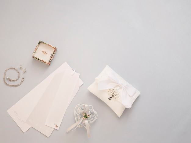 Minimal flat lay with wedding accessories on light background.