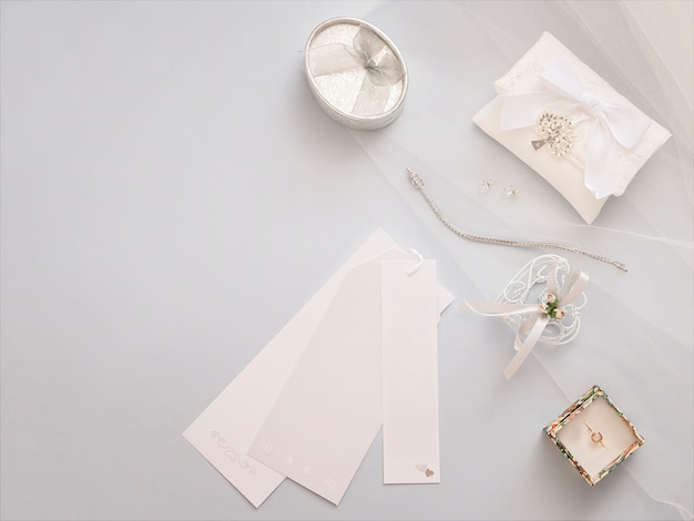 Minimal flat lay with wedding accessories on light veil background.